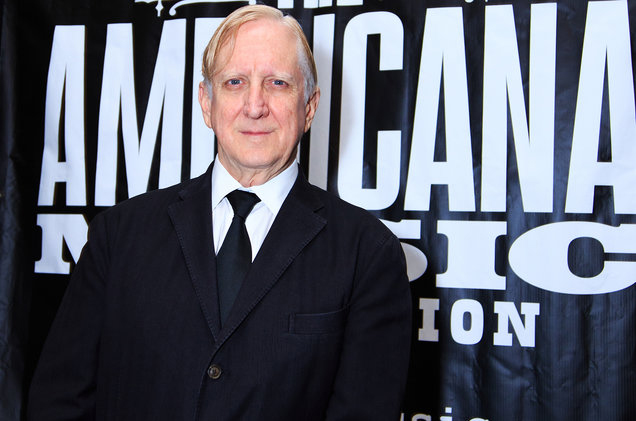 t-bone burnett in a suit and tie stands in front of an Americaa Music Fest poster