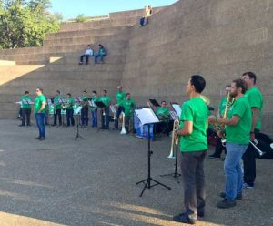 Symphony musicians perform in green union t-shirts at a public park