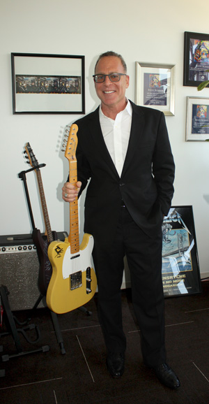 Steve Schnur poses in black suit, no tie, holding guitar