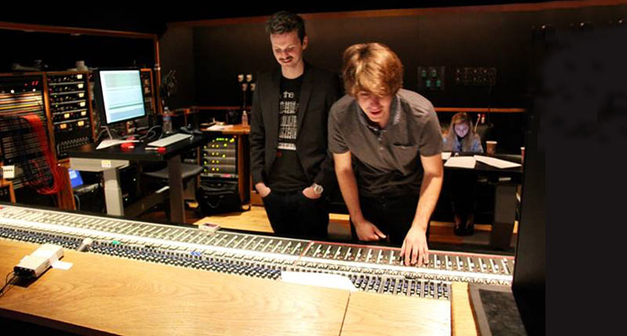 Composer John Hanson and producer Kyle Biane iwork the sliders at the mixing board.
