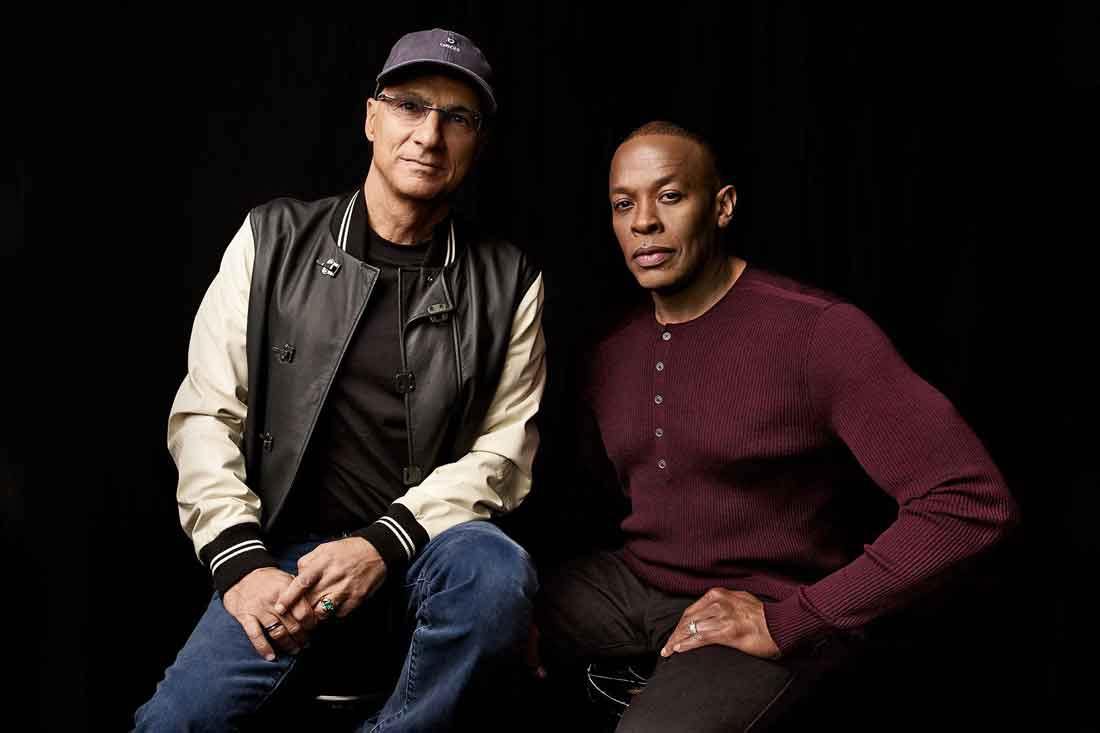 Jimmy Iovine in a baseball jacket and Dr. Dre in a maroon sweater.