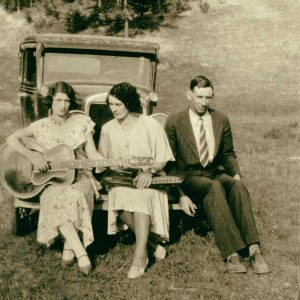 The Carter Family trio sit on the front bumper of car in a field.
