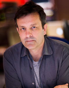 Composer Rupert Gregson-Williams looking casual in a gray t-shirt with steel-colored button-up on top.