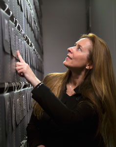 Allison McGourty touches index finger to a tall metal wall of music archives, looking upward