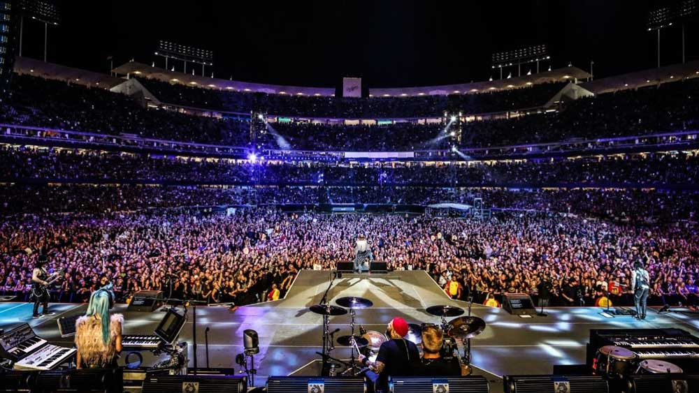 View from the band's perspective onstage looking into a vast arena packed with fans.