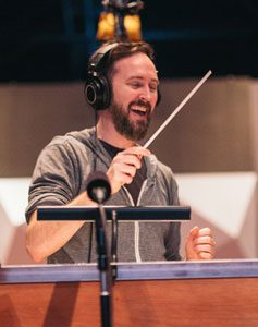 Composer Jeremy Turner conducting with baton and a big smile