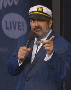 Jonathan Kimmel, a burly bearded man, dances with a microphone in a jaunty sailor cap and dark blue suit jacket.