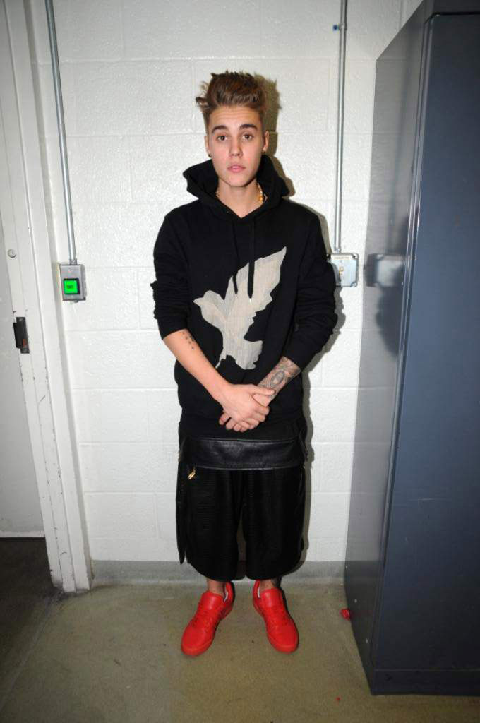Justin Bieber commits a fashion crime in calf-length baggy black shorts that look like a skirt, bright red shoes and a black hoodie emblazoned with an eagle.