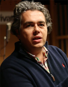 Lorne Balfe, his wavy gray hair swept back, in a navy blue Ralph Lauren Polo pullover with a plaid shirt beneath.