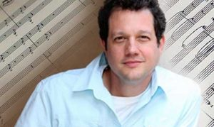 Michael Giacchino portrait with background of sheet music