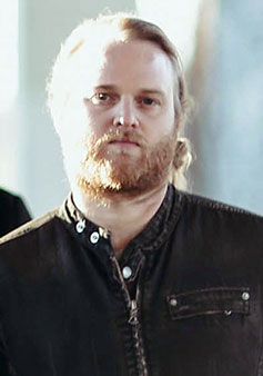 Dramatic image of bearded Michael Stein, outfitted in a black shirt, with his blonde hair pulled back in a pony-tail, has hard light streaming in from the left, obliterating detail on that side of his face.