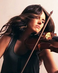 Composer Natalie Holt passionately plays the violin, her long dark hair cascading as if in a breeze