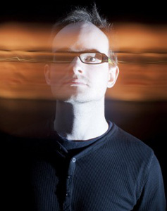 Rael Jones poses with a motion blur effect that appears to make his head move from the left to right portion of the frame.