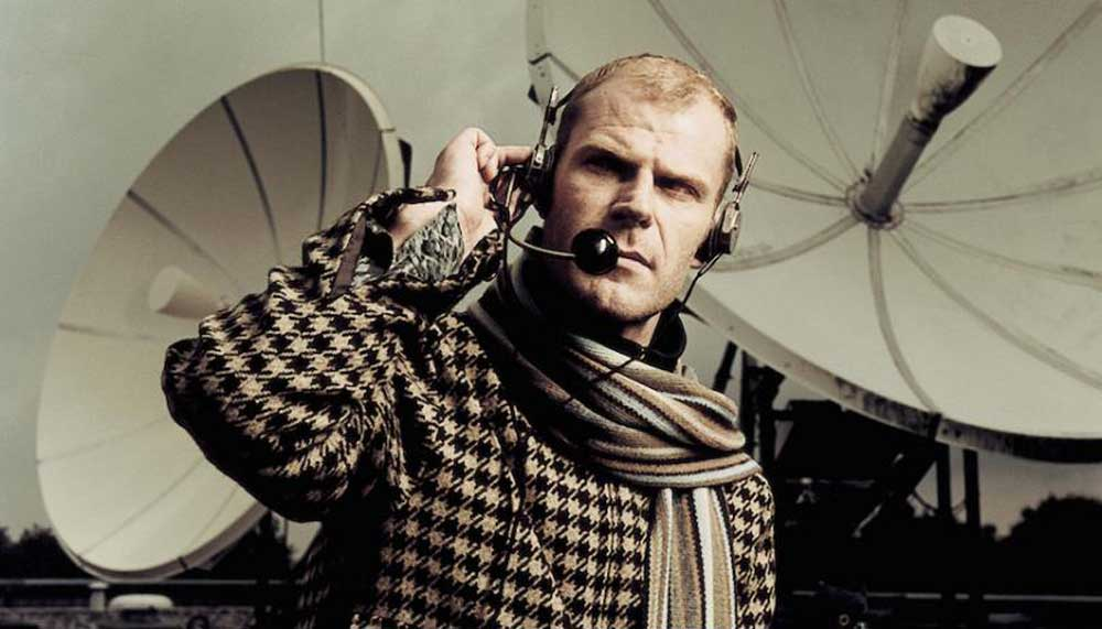 Tom Holkenborg poses in a houndstooth checked jacket with a headset, in front of satellite dishes.