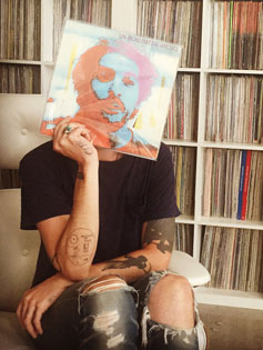 Zach Cowie sits in front of a wall of records, holding a vinyl LP with the an image of a face on it in front of his own face, becoming one with the music.
