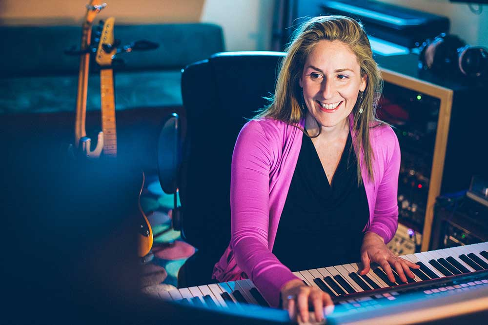 Ronit Kirchman at the keyboard in a pink sweater, with guitars in background.