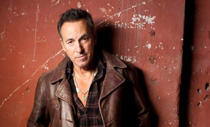 Bruce Springsteen in a brown leather jacket against a terra cotta colored wall.