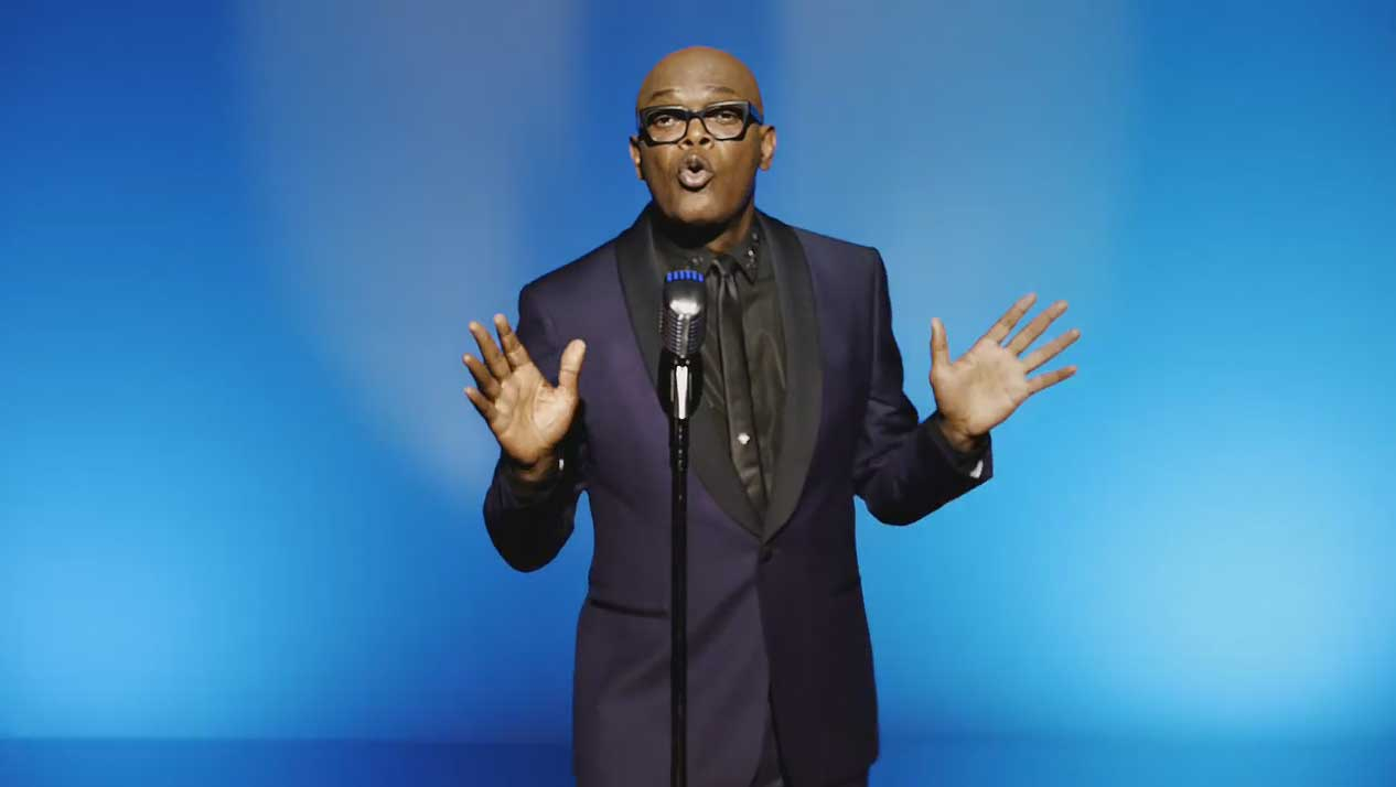 Samuel L. Jackson looks suave in black-on-black suit, singing with hands raised at microphone
