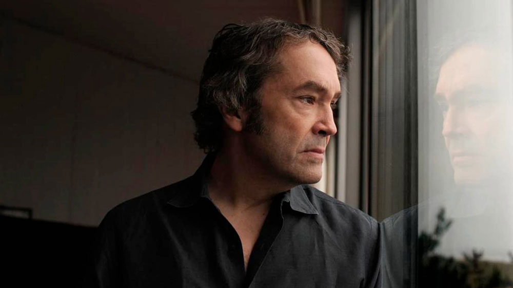 Carter Burwell reflects through a pane