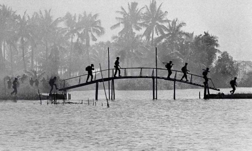 Soldiers walk across a footbridge in Vietnam.